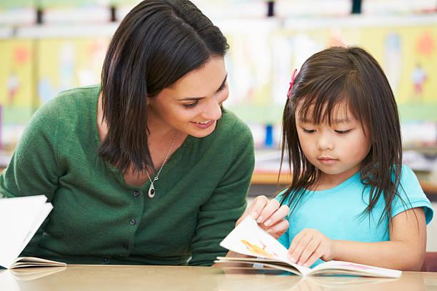 scolaro elementare con insegnante di lettura in classe - two students together asian foto e immagini stock