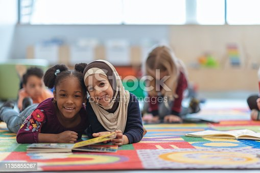 Two girls are laying on the carpet in their classroom. They are smiling at the camera while reading a book.