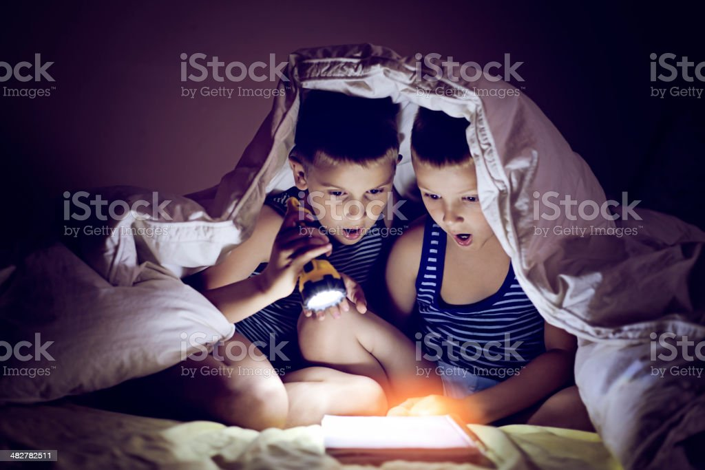 Reading with a flashlight stock photo
