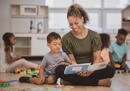 A preschool boy of Hispanic ethnicity sits next to his teacher as she is reading him a book on the classroom floor.