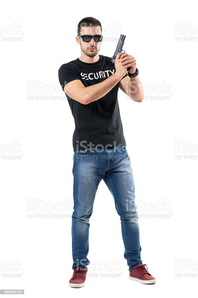 Ready alerted undercover officer holding gun in both hands looking at camera. stock photo