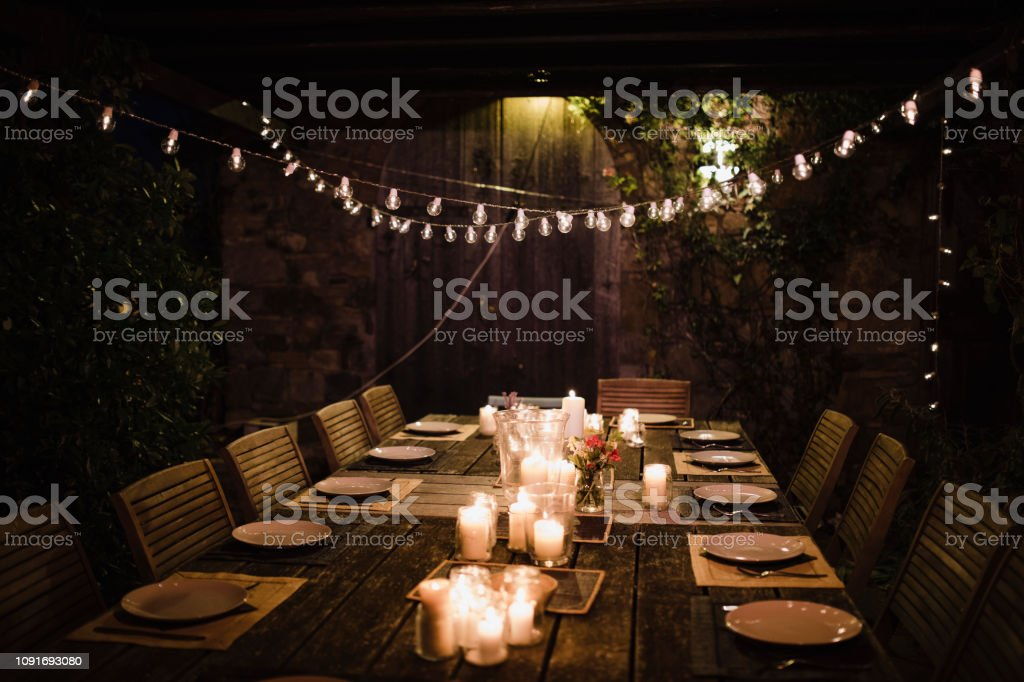 Night shot of a dressed garden table illuminated by candles and...