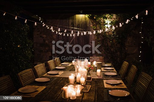 Night shot of a dressed garden table illuminated by candles and string lights.