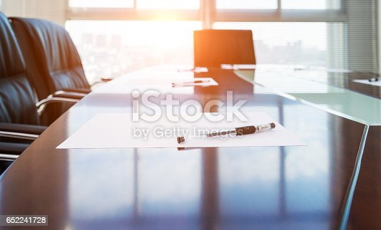 Corporate boardroom with blank paper set for the meeting.