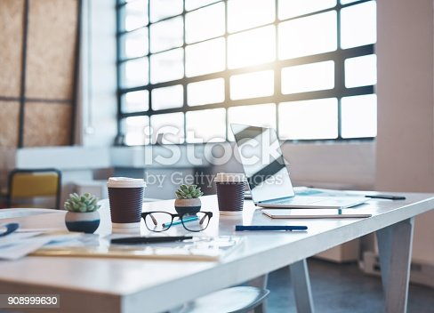 Shot of a laptop, papers and coffee cups on an empty boardroom table in the office