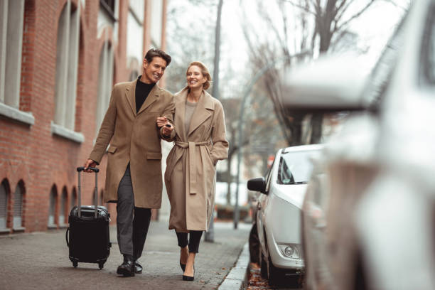 Ready for a trip Smiled smart elegant couple is walking to the car in the street. He is pulling the suitcase and unlocking the car with the remote key. georgijevic frankfurt stock pictures, royalty-free photos & images