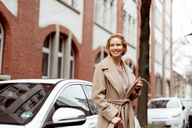Ready for a trip The woman next to the car is waiting and looking down the street. georgijevic frankfurt stock pictures, royalty-free photos & images