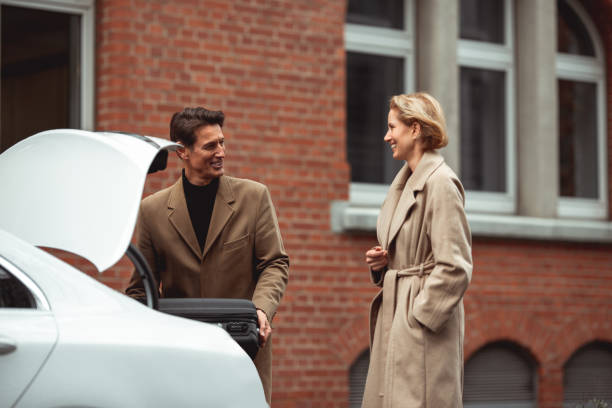Ready for a trip Two good looking german adults are preparing to go for a road trip. He is putting a suitcase in the trunk. georgijevic frankfurt stock pictures, royalty-free photos & images