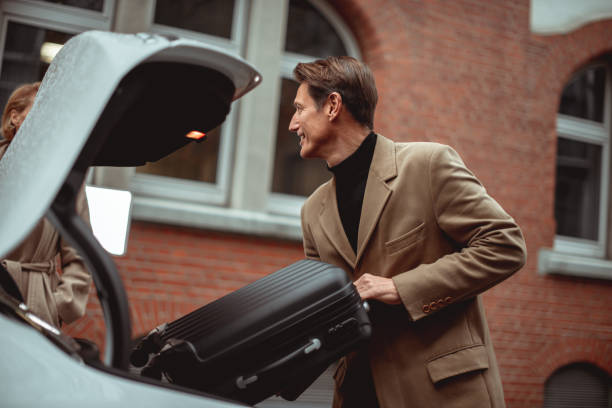 Ready for a trip Good looking 50-year-old man is putting luggage in the trunk of his car. georgijevic frankfurt stock pictures, royalty-free photos & images