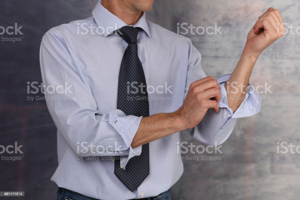 Ready for action. Businessman Rolling Up Sleeves. stock photo