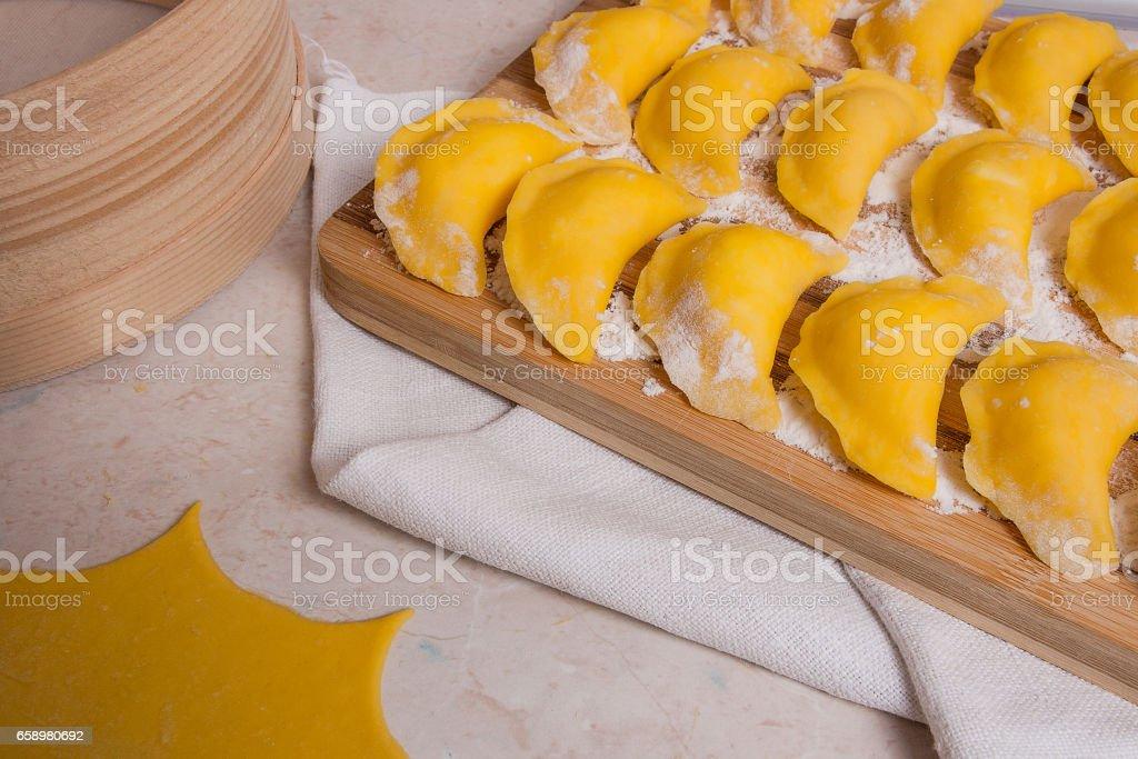 Ready for boiling vareniki, dumplings, pierogi on wooden cutting board royalty-free stock photo