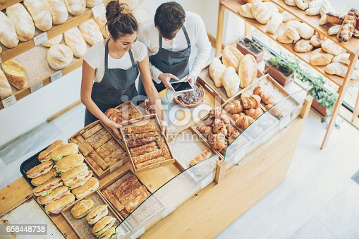 Top view of young couple of bakers inside the bakery, holding a digital tablet and arranging the pastry