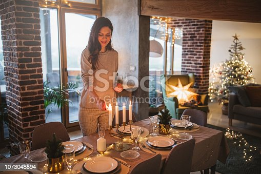 Young woman celebrating Christmas at home and prepare Christmas meal. Home is decorated with Christmas ornaments and lights.