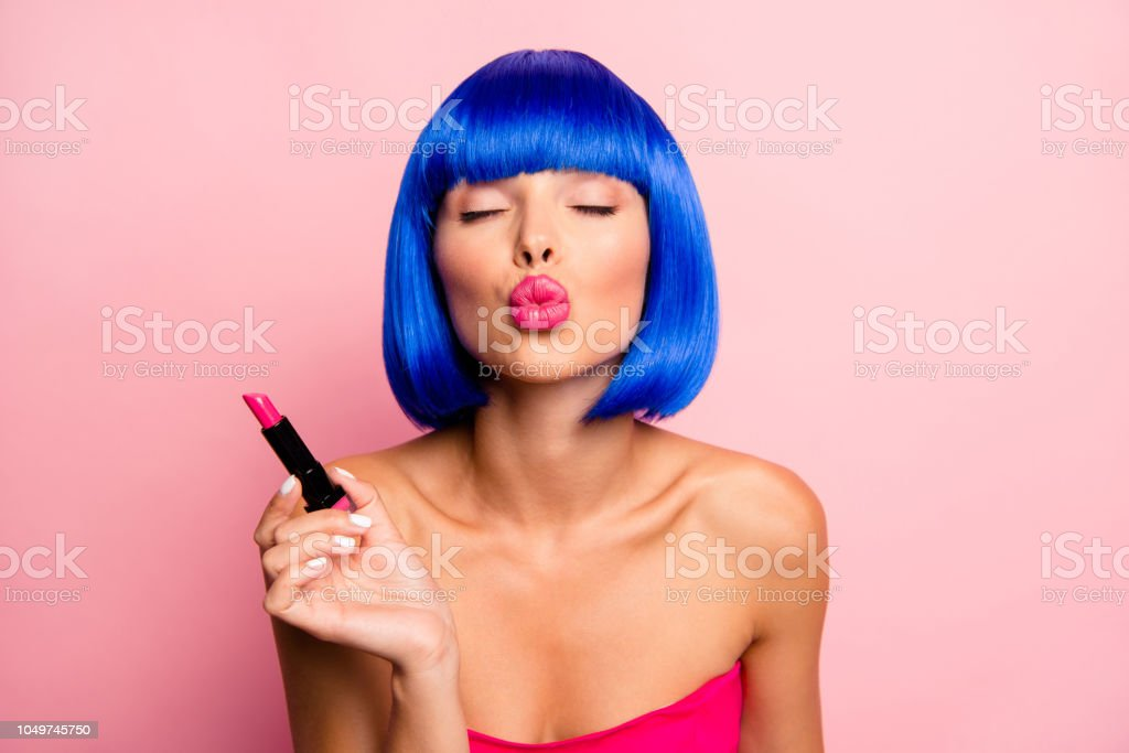 Ready for date! Charming, attractive, dreamy girl holding red lipstick pouting lips for send air kiss isolated on pastel pink background stock photo