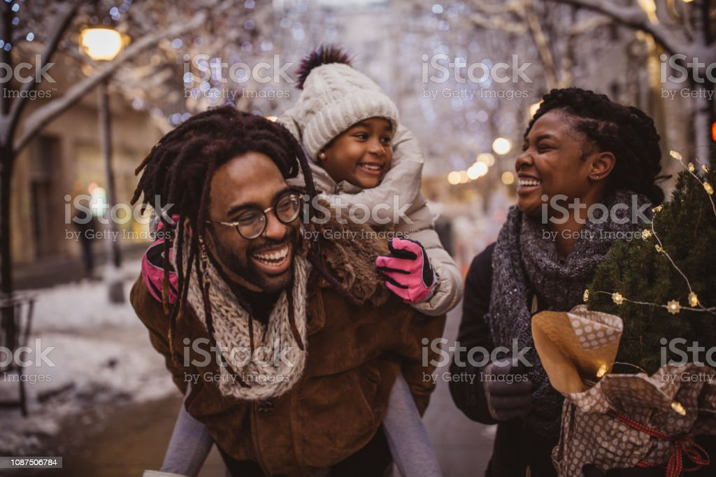 Ready for holidays Young family preparing for Christmas holiday. They walking on street and carrying Christmas stuff. 25-29 Years Stock Photo
