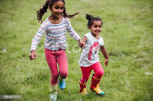 Two happy sisters holding hands and running through a field.