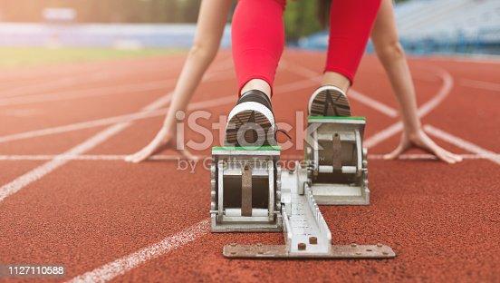 Female athlete on the starting line on stadium track preparing for run. Ready for run concept