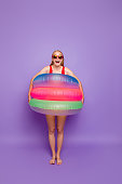 Ready for summer! Concept of a fun vacation on the beach. Full-length portrait of girls with colorful life rings on the waist isolated on violet background