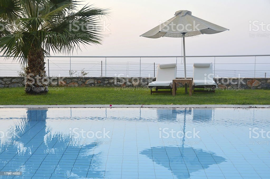 Ready for summer: sunbeds by the pool royalty-free stock photo