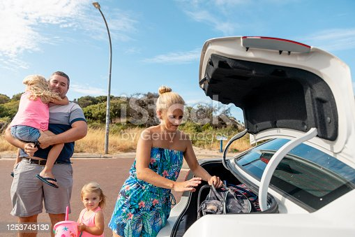 A caucasian family visiting the beach on a sunny day in Perth, Australia. They are unpacking the trunk of their car.