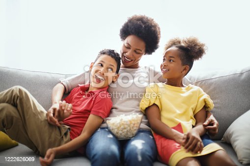 Happy family of three enjoying at home. They are eating popcorn while watching television.