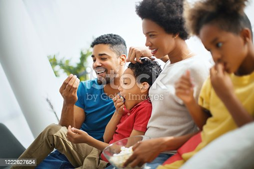 Happy family enjoying at home. They are eating popcorn while watching television.