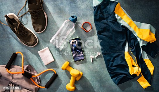 Mobile phone surrounded with various fitness-related objects, clothes, equipment and technology, all in a blue-toned overhead composition.
