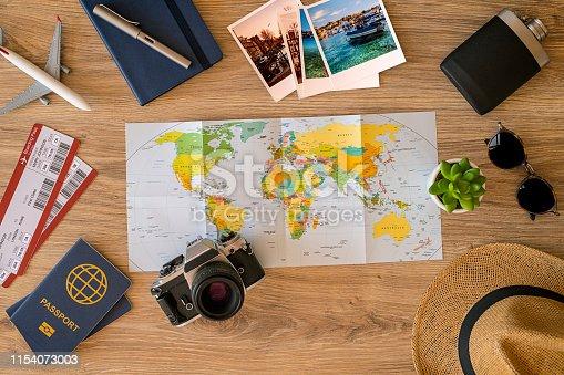 Travel stuff on desktop: map, sun glasses, camera, tickets, passport etc.