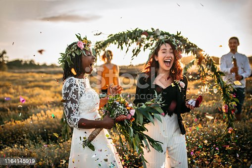 Lesbian wedding party. Two brides on wedding ceremony, surprised with confetti standing in a front of outdoor wedding arch