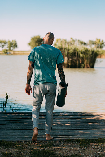 Man walking towards the spot he's picked for his daily yoga routine, self care concept.