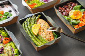 istock Ready healthy food catering menu in lunch boxes fish and vegetable packages as daily meal diet plan courier delivery with fork isolated on black table background. Take away containers order concept. 1262278932