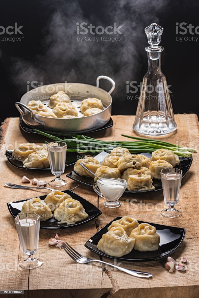 Ready hot manti on black plates, vodka in the countess and three piles on an oak table-top стоковое фото