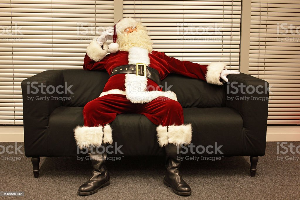 ready santa claus waiting for christmas job sitting on sofa stock photo