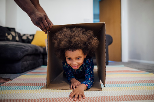 Mixed race girl crawling through a cardboard box in the sitting room at home, her unrecognisable father is holding the box up for her.