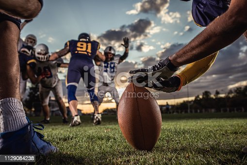 Unrecognizable American football player preparing a ball for kick off on a playing field.