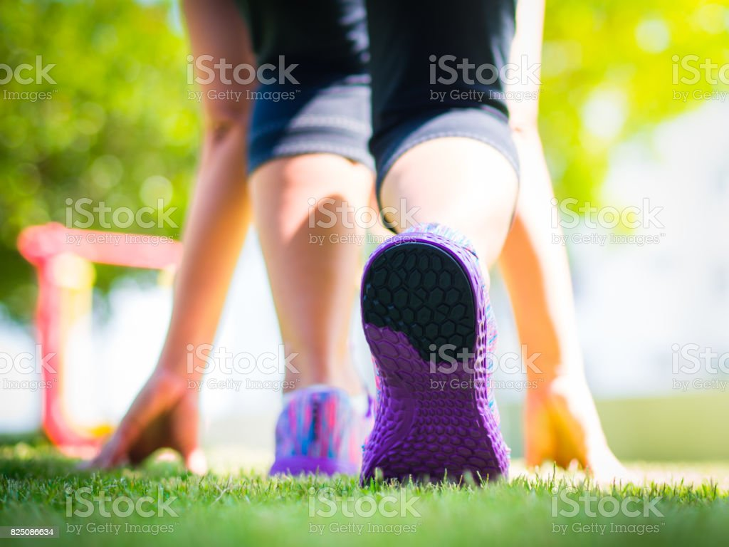 Ready steady go. Closeup of running shoes on grass, young lady on start position and going to run in park. stock photo