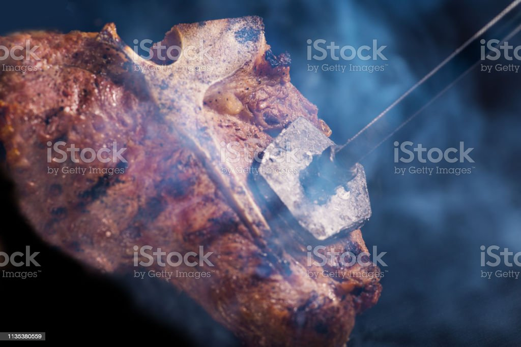 Ready T-bone   steak on which burns the stigma of the logo stock photo