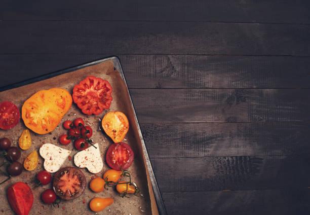 Bereit, Tomaten verschiedener Art mit Käse und Thymian auf schwarzem Hintergrund zu backen – Foto
