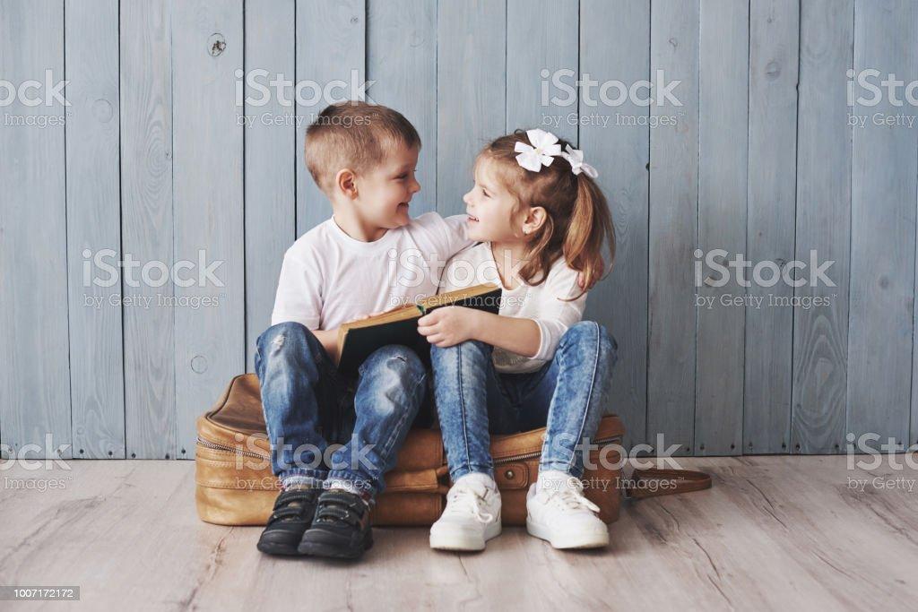 大きな旅行する準備ができています。幸せな少女と少年の読書興味深い本大きなブリーフケースを運ぶと笑顔します。旅行、自由と想像力の概念 ストックフォト