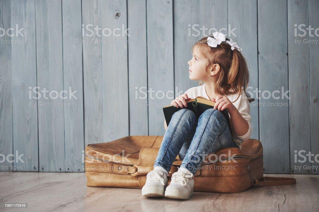 大きな旅行する準備ができています。大きなブリーフケースを運ぶと笑顔を備えた幸せ小さな女の子読書興味深い。旅行、自由と想像力の概念 ストックフォト
