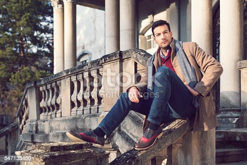 Young, handsome man casually sitting on the stairs fence of an old, rustic house