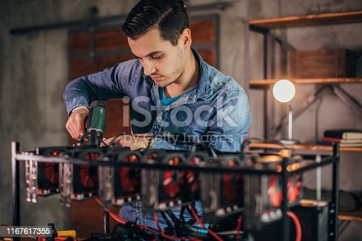 One young man installing gear for mining bitcoin, using cordless screwdriver.