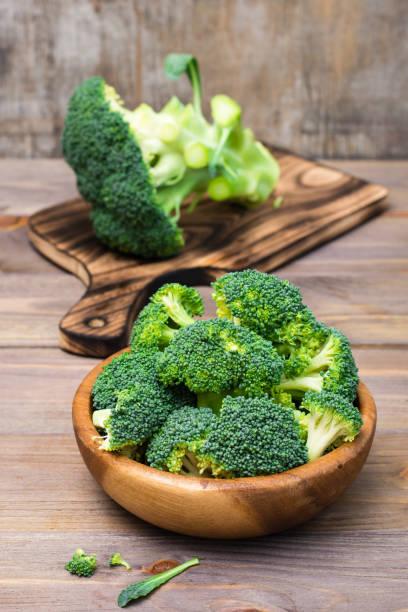 Taze ham brokoli yemeye hazır bir ahşap tabak ve ahşap bir masa üzerinde bir kesme tahtası üzerinde çiçeklenme ayrılır. Sağlıklı yaşam tarzı, beslenme ve sıfır atık kavramı stok fotoğrafı