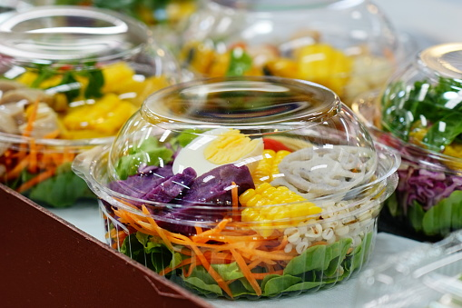 Salad of fresh vegetables and healthy fruit in clear plastic box  for sale in market