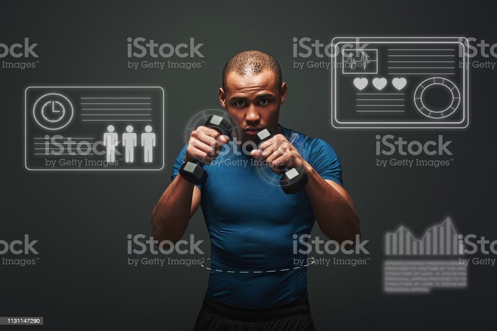 Muscular sportsman with dumbbells flexing muscles and looking at the...