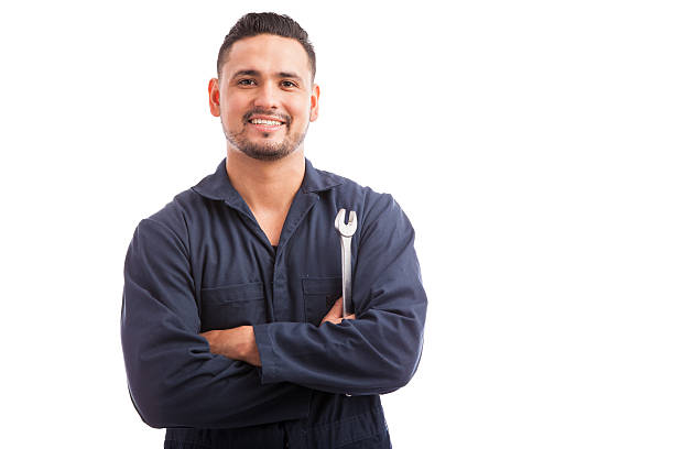Ready to fix your broken car Portrait of a young mechanic holding a wrench and smiling, ready to fix cars repairman stock pictures, royalty-free photos & images