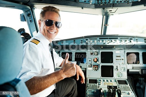 Rear view of confident male pilot showing his thumb up and smiling while sitting in cockpit