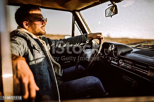Young good-looking man driving in car alone, on country side, on sunny summer day, photo is taken in car from 1980 year