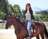 Portrait of a gorgeous cowgirl sitting on her horse