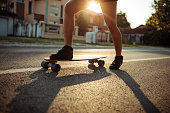 Waist down shot of a girl riding a longboard on the street